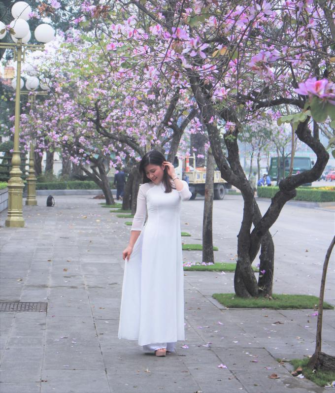 Trang phục áo dài trắng truyền thống, giản dị khoe sắc bên những cánh hoa ban tím dịu dàng.