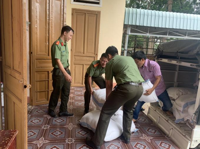 Các chiến sĩ công an hồ hởi khuân gạo quyên góp được để làm bánh tét
