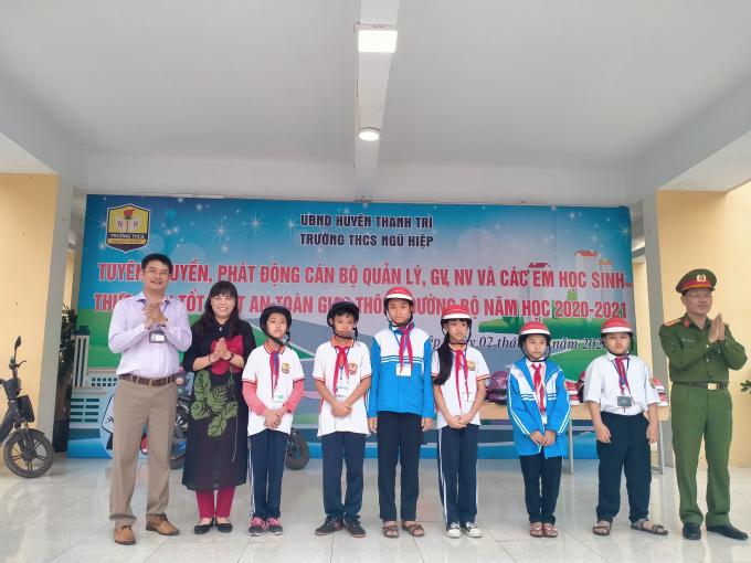 Bà Nguyễn Thị Tuyết Lê - TP Giáo dục và Thượng tá Nguyễn Mạnh Dầu tặng mũ bảo hiểm cho các em (Ảnh Mạnh Hùng)
