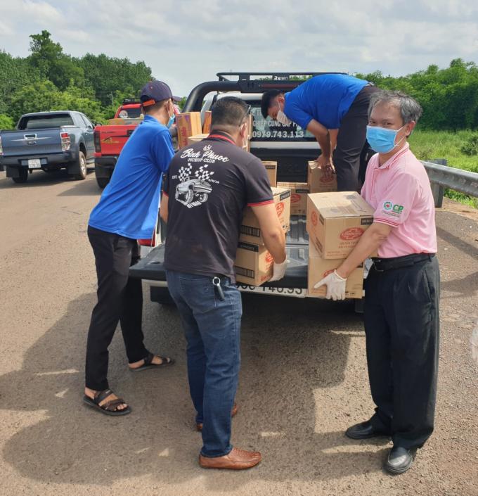 Anh Lê Đình Công - Giám đốc công ty Cổ phần chăn nuôi CP Việt Nam - chi nhánh Bình Phước (bìa phải) đang cùng các thành viên CLB xe bán tải Bình Phước và ĐVTN nhanh chóng vận chuyển quà tặng để hỗ trợ huyện Ô Răng