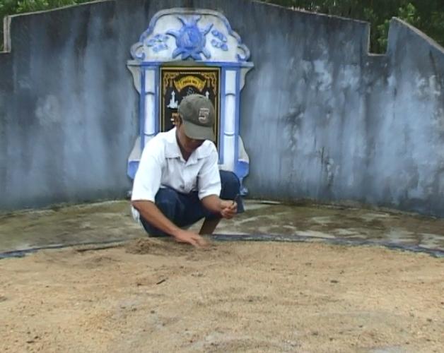 Một người đang nhặt đinh bị đóng ở mộ người thân.