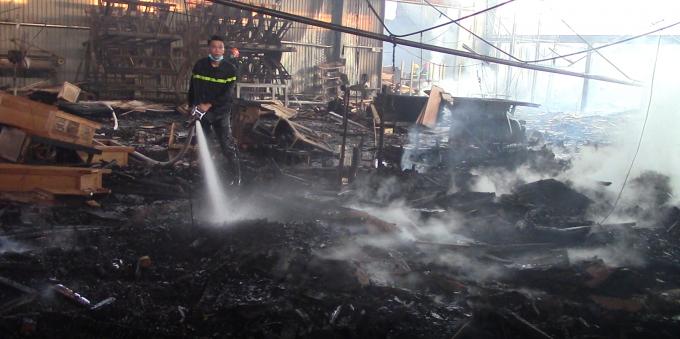 Một phần nhà xưởng đổ sập, nhiều bàn ghế và nguyên liệu bị thiêu rụi