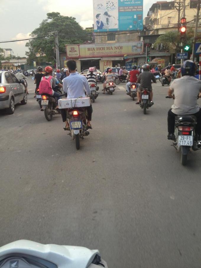 Một bạn trẻ khi tham gia giao thông không đội mũ bảo hiểm, vô tư sử dụng điện thoại khi lái xe (ảnh Thanh Huyền)