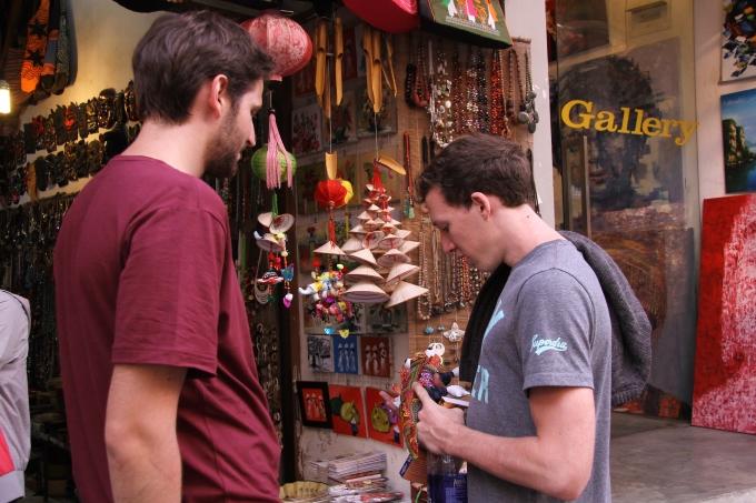 Một du khách người Pháp đang chăm chú xem các sản phẩm len tại phố Đinh Liệt