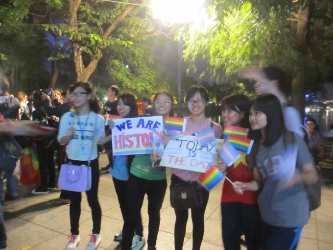Các bạn trẻ đeo băng rôn khẩu hiệu chúc mừng người chuyển giới tại Hồ Gươm (Ảnh: Mẫn Nhi)
