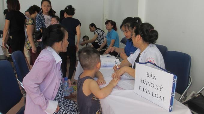 Trẻ được gia đình đưa đến uống Vitamin A cũng như cân được các y tá của Trạm y tế phường hướng dẫn đăng ký và phân loại độ tuổi trẻ. (Ảnh: Thu Hường)