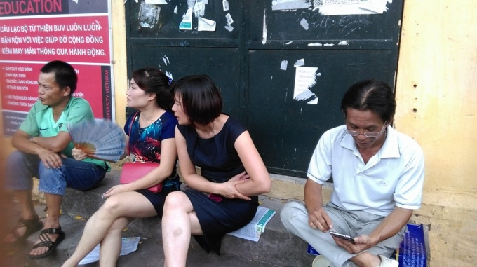 Phụ huynh ngồi chờ con trước điểm thi trường THPT Việt Đức vớí tâm trạng hồi hộp, lo lắng. (ảnh: Thu Hường)