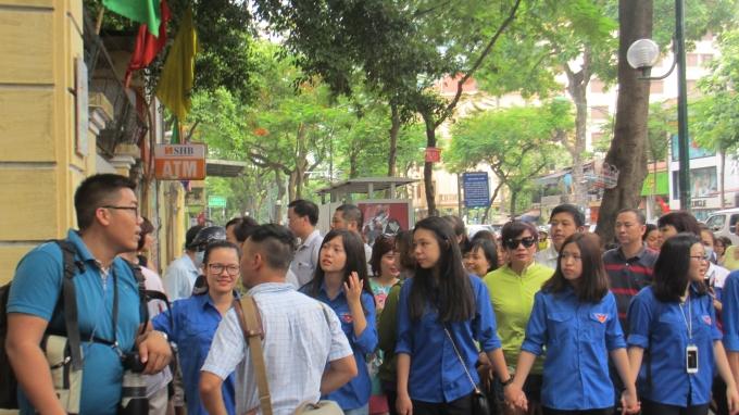 Phụ huỳnh và các bạn tình nguyện đều hướng mắt về cổng trường đề chào đón những sĩ tử hoàn thành bài thi sáng nay. (ảnh: Thu Hường)