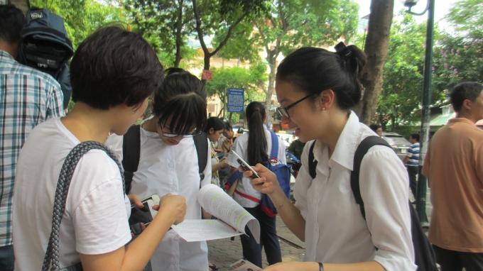 Hai bạn thí sinh cùng mẹ xem lại đề thi môn Ngữ Văn. (ảnh: Thu Hường)