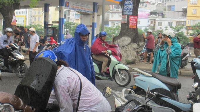 Mặc dù trời mưa to, nhưng hầu hết các bậc phụ huynh đều sẵn sàng đội mưa để cùng con mình trải qua môn thi Toán. (Ảnh: Thu Hường)