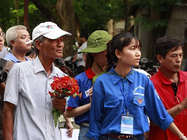 Ông Tạ Minh Đức (Hà Đông) cầm bó hoa nhỏ và hướng đôi mắt về phía cổng trường chờ cháu gái để tặng bó hoa nhỏ.