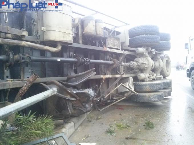 Xe tải hất tung dải phân cách, lật giữa đường.