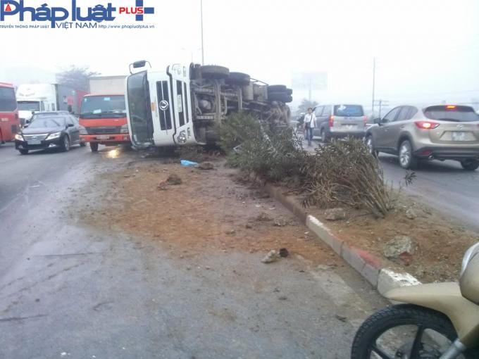 Chiếc xe tải bị lật nằm ngang giữa 2 làn đường.