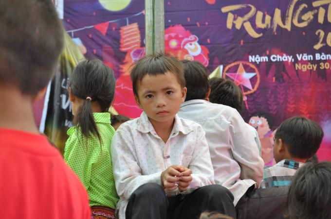 Một em học sinh lớp tiểu học ngồi dưới sân trường cùng các bạn chờ đến tối để đón Trung Thu.