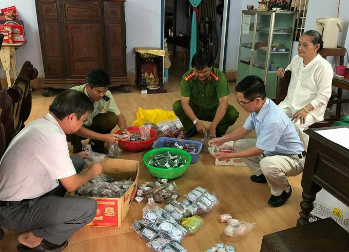 Lực lượng chức năng kiểm tra số thuốc mà bà Xuyến bán cho bệnh nhân (VietnamNet)