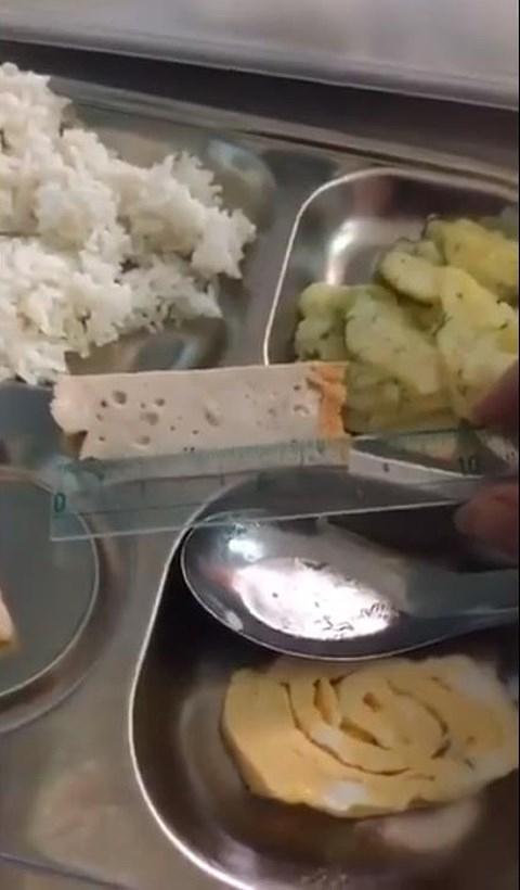 Miếng chả mỏng dính được phụ huynh dùng thước đo (ảnh cắt từ clip)