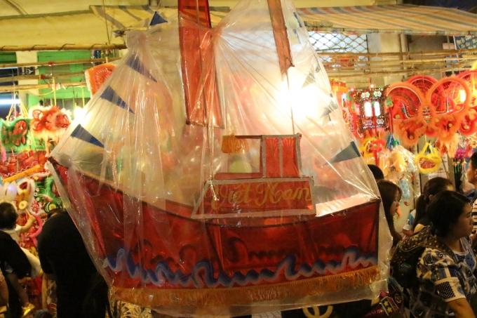 Một chiếc lồng đèn hình con thuyền, bên trên có chữ Việt Nam.