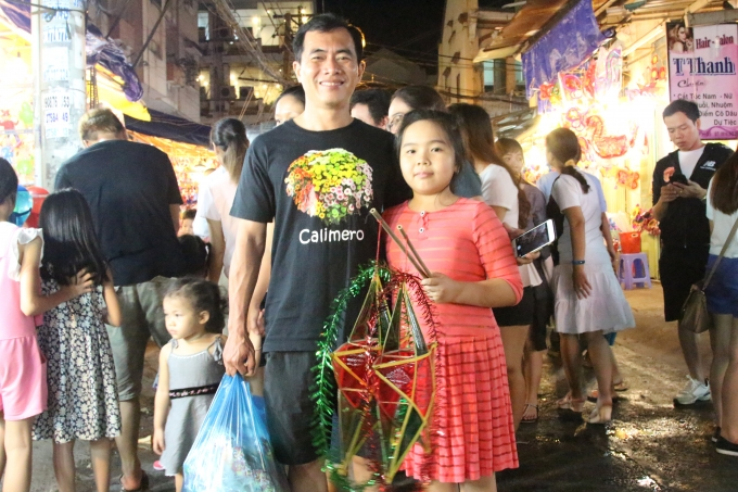 Bé gái này được bố mua cho hai chiếc lồng đèn hình ngôi sao. Trước khi ra về, hai bố con cũng nhờ phóng viên chụp dùm tấm hình để làm kỉ niệm.