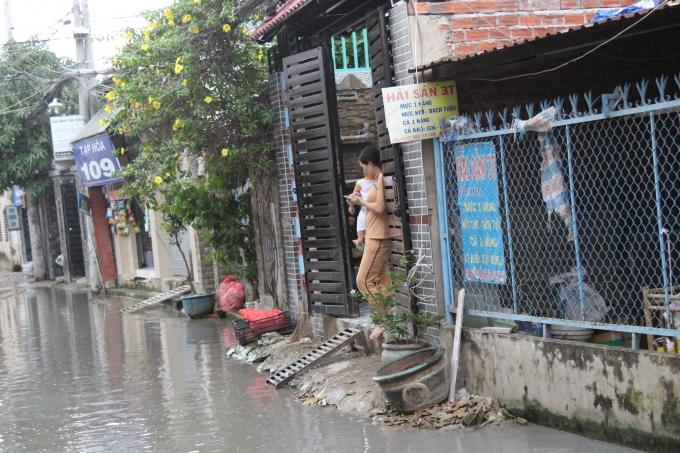 Nước ngập thế này thì chỉ có thể đứng trong nhà nhìn ra đường.
