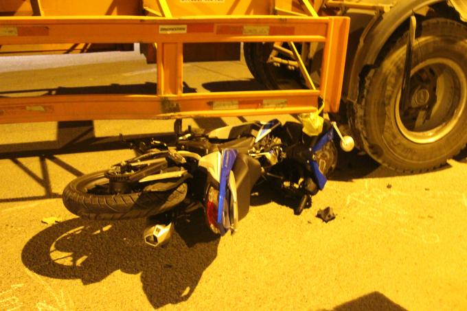 Xe máy lọt dưới gầm xe container.