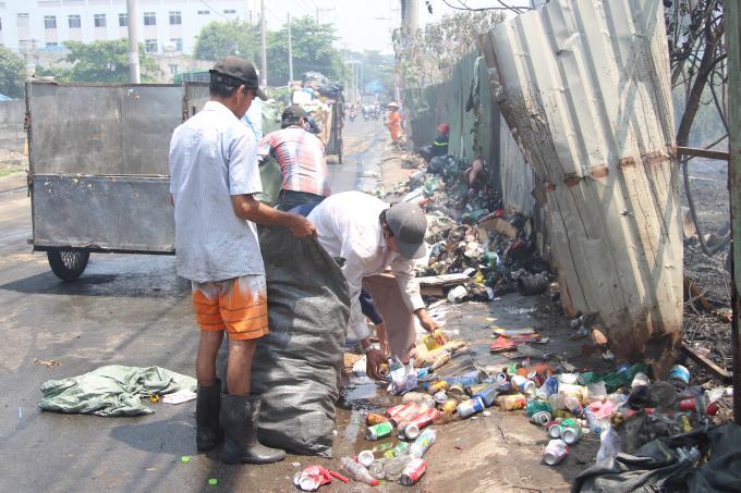 Công nhân thu gom rác sau vụ cháy.