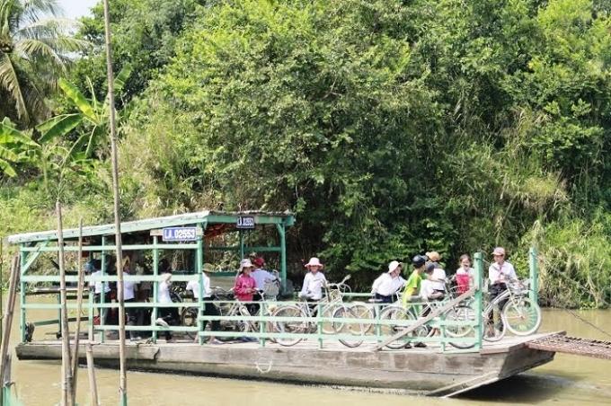 Những em học sinh phải đi phà qua bên kia sông để đi học.