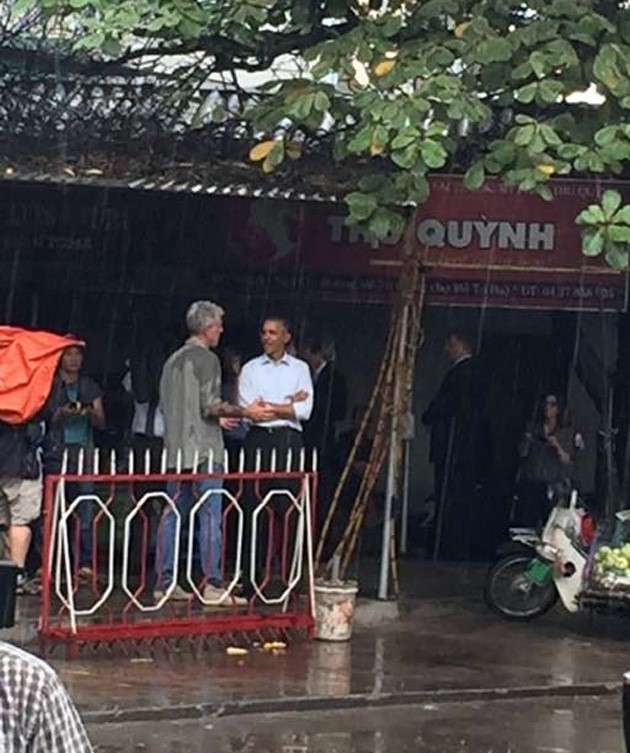 Tổng thống Obama đứng trú mưa trong quán trà đá.