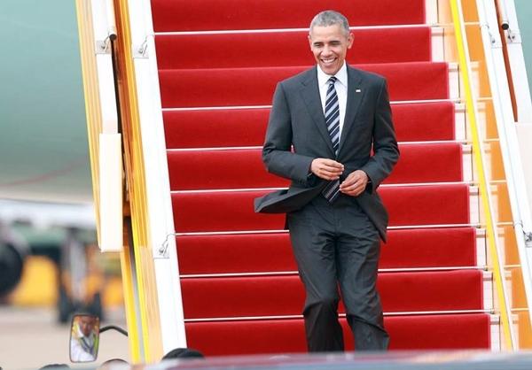 Ông Obama bước xuống sân bay Tân Sơn Nhất trong chiếc áo sơ mi trắng, vest đen. Ông tươi cười vẫy tay chào mọi người đang đón ở sân bay.(Ảnh: VnExpress).