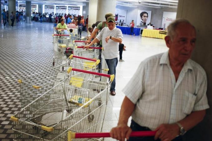 Người mua mệt mỏi vì xếp hàng dài mua hàng tại siêu thịBicentenario (Ảnh: Reuters).