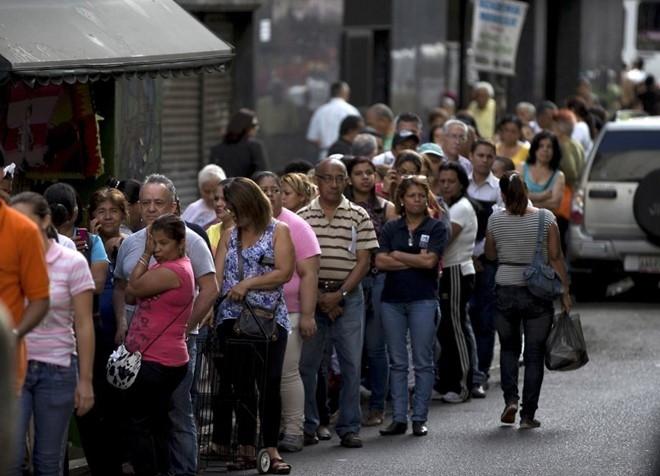 Người dân xếp hàng chờ mua nhu yếu phẩm bên ngoài một siêu thị ở thủ đô Caracas. (Ảnh: AP).