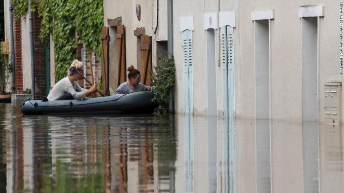 Hai phụ nữ cố gắng vào nhà bằng thuyền. (Ảnh: Getty)
