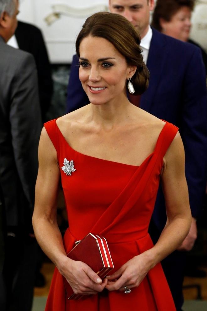 Công nương xứ Cambridge quyến rũ và dịu dàng trong chiếc váy đỏ 1.200 USD của hãng Peen khi tham dự tiệc tối.Cô đeo trâm hình lá phong từng được cố nữ hoàng Anh sử dụng trong chuyến thăm Canada năm 1939 và hoa tai lấp lánh khiến bộ váy càng thêm nổi bật.Chiếc ví cầm tay và đôi giày cao gót được phối cùng màu, nâng tổng giá trị bộ trang phục lên hơn 2.000 USD.(Ảnh: Reuters)