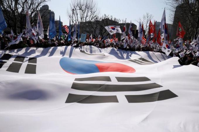Hàng trăm người ủng hộ tổng thống Hàn Quốc vừa bị phế truất đã vượt rào chắn, đánh cảnh sát bằng những cây cờ họ mang theo để biểu tình phản đối quyết định của Tòa Hiến pháp. (Ảnh: Reuters)
