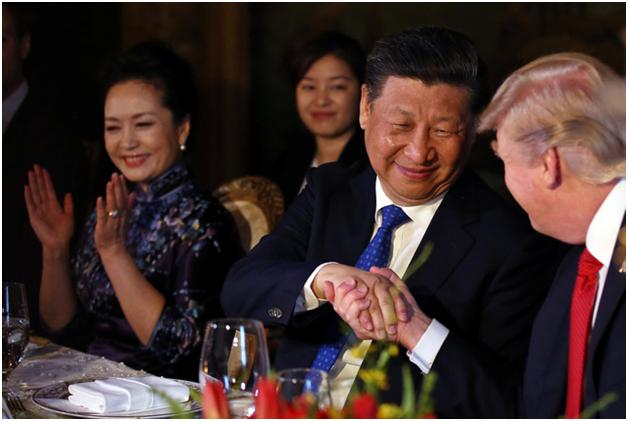 Bà Bành Lệ Viện vỗ tay khi hai nhà lãnh đạo bắt tay. Tới thăm Mỹ lần này, đệ nhất phu nhân Trung Quốc chọn bộ trang phục kín đáo và nền nã, khác với phong cách thời trang có phần thoải mái hơn của bà Melania Trump. (Ảnh: Reuters)