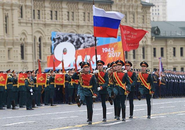 Sĩ quan Trung đoàn Cận vệ Độc lập số 154 Preobrazensky mang quốc kỳ Liên bang Nga và Quân kỳ Quyết thắng dẫn đầu các khối duyệt binh tiến qua Quảng trường Đỏ.