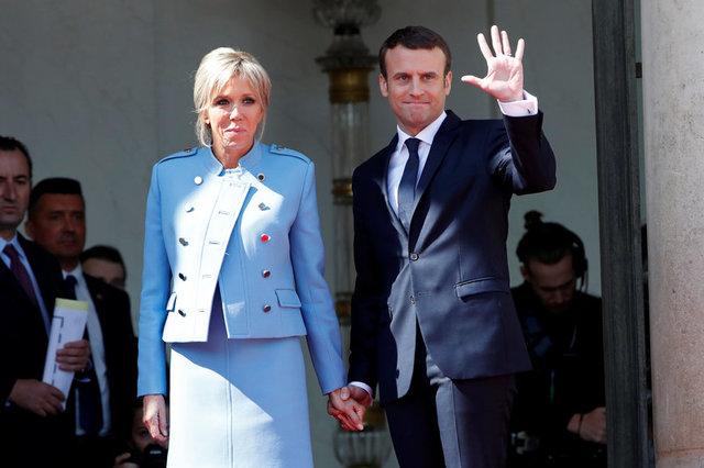 Ông Emmanuel Macron nắm tay phu nhân Brigitte Trogneux khi vẫy chào người tiền nhiệm Francois Hollande sau cuộc chuyển giao quyền lực. (Ảnh: Reuters)