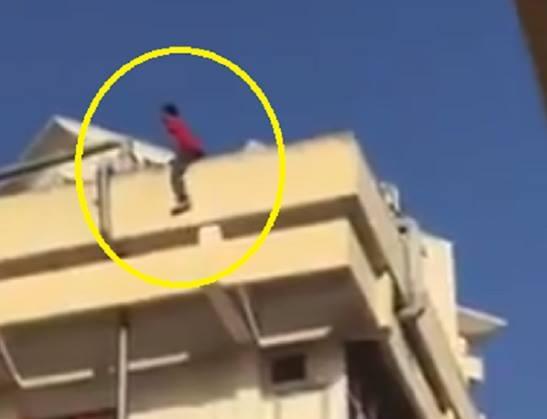 Nam sinh viên cheo leo trên lan can tòa nhà (Ảnh cắt từ clip).
