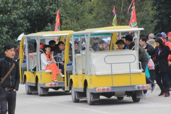 Du khách đi xe điện vào khu vực diễn ra lễ khai hội.