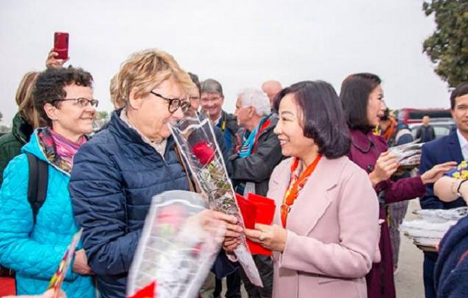 Ba Vũ Thị Thu Thủy trao hoa và lì xì mừng tuổi những du khách đầu tiên đến với Vịnh Hạ Long trong ngày mùng 1 tết âm lịch.