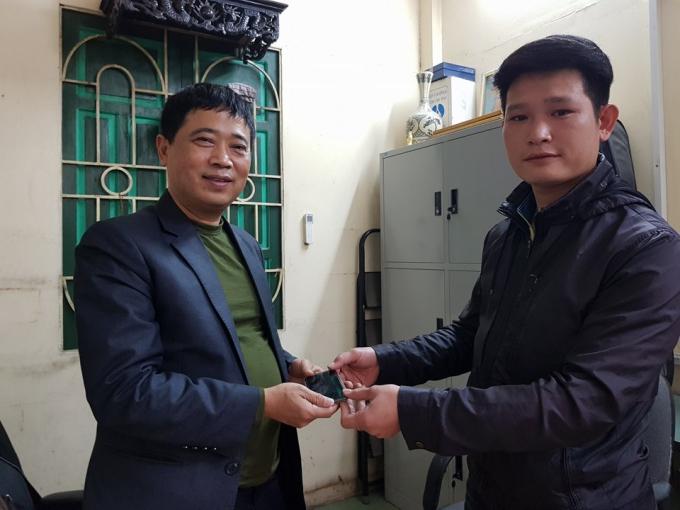 AnhNguyễn Anh Tuấn (bìa phải), vui mừng nhận lại tài sản của mình từ lãnh đạo Đội TTGT quận Hoàn Kiếm.