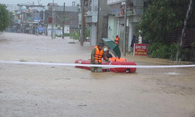 Lực lượng chức năng dùng xuồng phao cứu hô di dời người dân tới nơi an toàn.