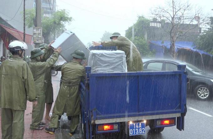 Lực lượng chức năng dùng xe chuyên dụng di chuyển tài sản của người dân đến nơi an toàn.
