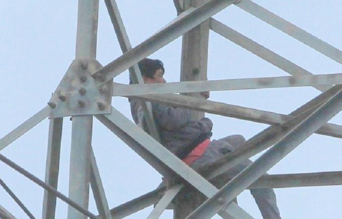 Người đàn ông nghi ngáo đá ngồi vắt vẻo trên cột điện cao thế nhiều giờ đồng hồ.