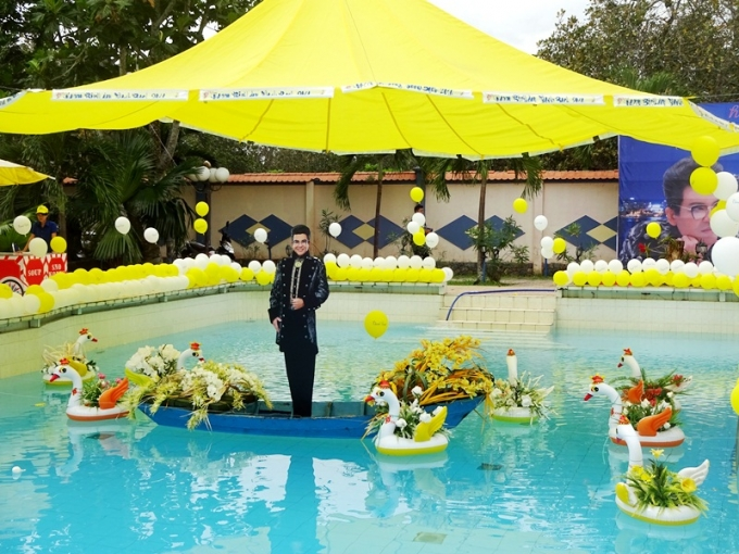 """Hình nghệ sĩ Thanh Bạch to bằng người thật trên thuyền hoa giữa hồ bơi trong """"vườn Thúy Nga""""."""