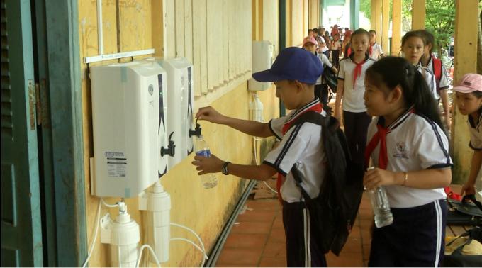 Các em học sinh vui mừng lấy nước sạch uống.