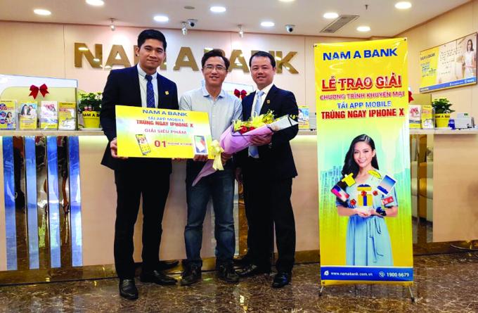 Ông Nguyễn Quang Thông - Giám đốc Trung tâm Ngân hàng số và ông Nguyễn Quốc Khánh - Giám đốc Nam A Bank Hòa Bình trao giải Siêu phẩm là 1 chiếc iPhone X cho Khách hàng Nguyễn Ngọc Dương.