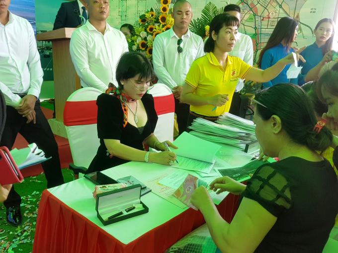 Bà Phạm Thị Hường (váy đen, bên trái ảnh), đại diện chủ đầu tư và khách hàng ký hợp đồng, bàn giao sổ hồng.