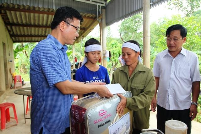 Bộ trưởng đến thăm và tặng quà cho gia đình chịu thiệt hại nặng nề do mưa lũ.