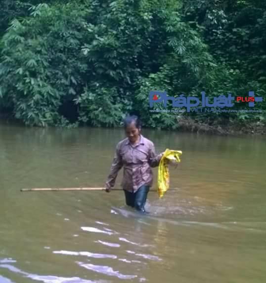 Người dân xã Thổ Bình tiếp tục vớt cá chết dưới làn nước suối lờ lờ đỏ đục.