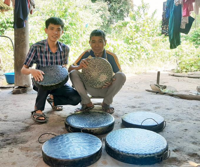 Tác giả (trái) và già làng Pang Ting Ha Thét bên bộ cồng chiêng 6 chiếc.